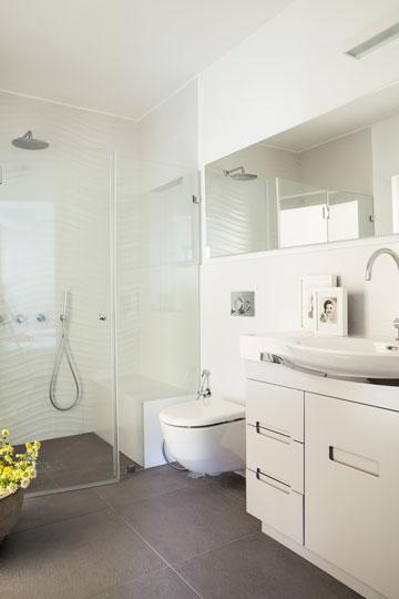 מקלחון עם ספסל ומראה ארוכה בחדר הרחצה של ההורים (צילום: איתי בנית)