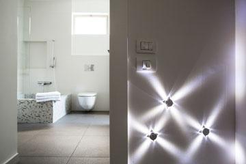 מנורות קטנות על הקיר מסמנות בלילה את הכניסה לחדר הרחצה המרכזי (צילום: איתי בנית)