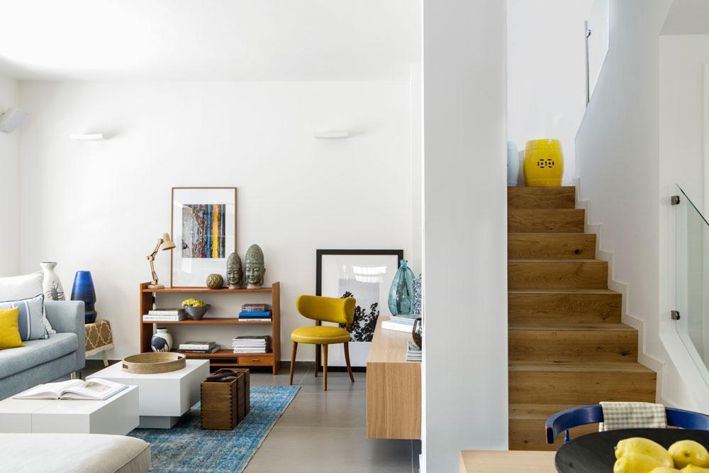 בני הבית לא אוהבים פרקט, ולכן רוצף הבית באריחים גדולים באפור-זית, אך המדרגות חופו בעץ אלון. לפני השיפוץ היה גרם המדרגות פתוח לסלון. הוא נתחם בקיר שעליו נתלה מסך הטלוויזיה (צילום: איתי בנית)