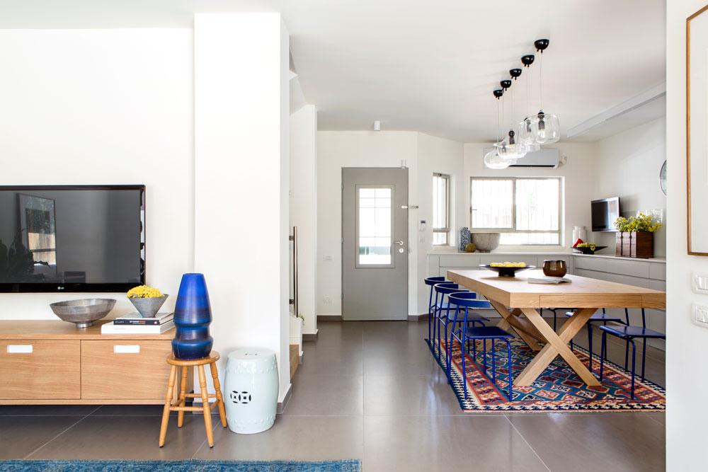 וכך נראה המטבח מכיוון הסלון. שטח קומת הכניסה 55 מ''ר, והיא כוללת מטבח, סלון, חדר עבודה ושירותי אורחים. גרם המדרגות, שנמצא מול פינת האוכל, חוצה את הקומה לשניים (צילום: איתי בנית)