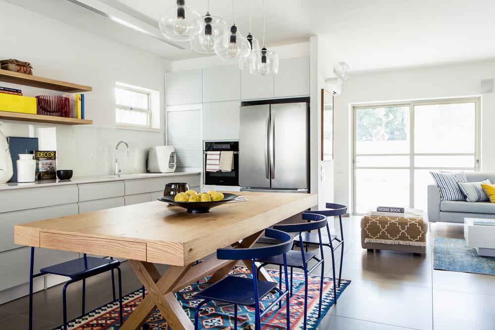 מבט מהמטבח לכיוון הסלון והיציאה לגינה. המטבח עוצב בצבעים שקטים, שמבליטים את כתמי הצבע: שולחן ומדפים מעץ אלון מבוקע, כסאות בכחול גואש ושטיח בכחול ואדום (צילום: איתי בנית)