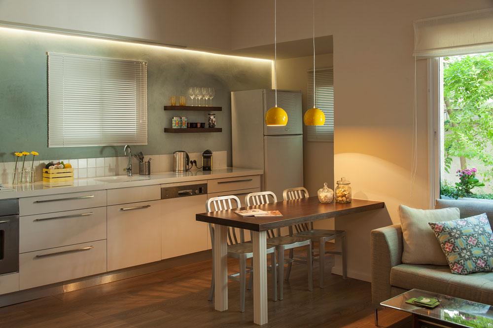 המטבח החדש. קיר תכלכל, אריחים לבנים ותאורת לד סביב הקורה, שנותנת מסגרת דקורטיבית למטבח גם בשעות היום (צילום: אסף הבר)