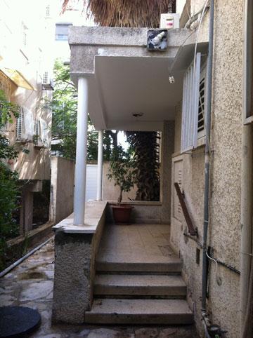 הכניסה לדירה הקטנה בקומת הקרקע, לא רחוק מהים (צילום: שירי בלום לאודן)