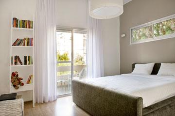 חדר שינה עם יציאה למרפסת שמקיפה גם את הסלון (צילום: גלית דויטש)