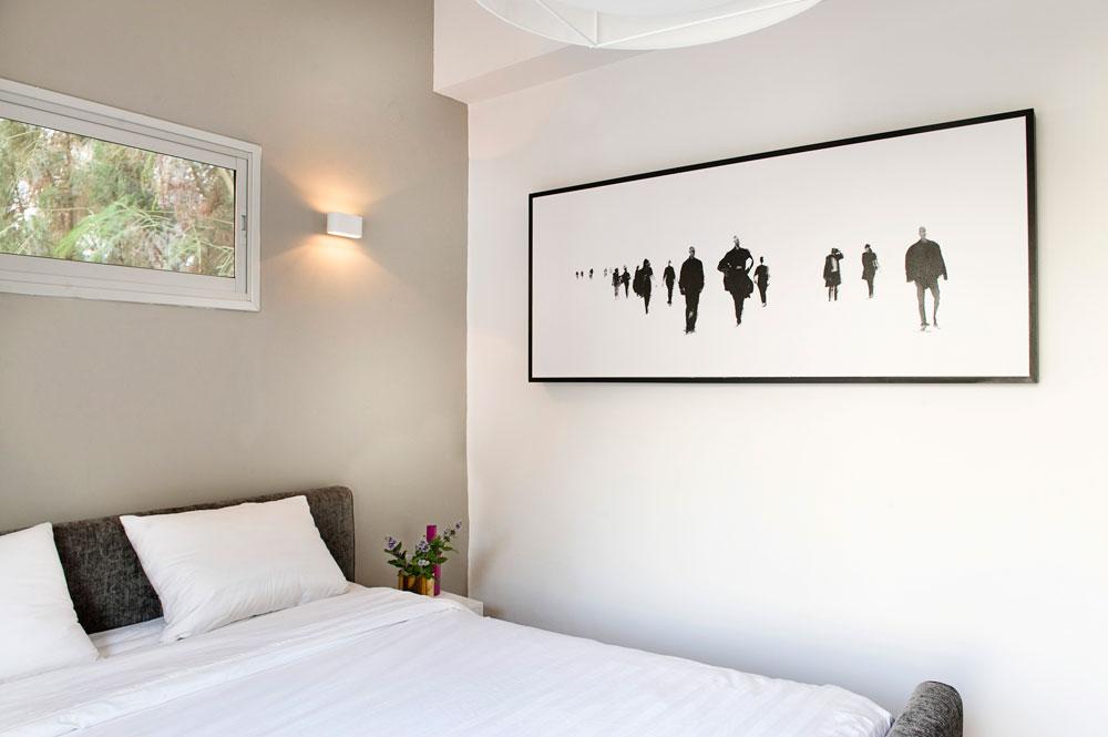 חדר שינה בהיר ומודרני גם הוא, עם מיטה וקיר בגוני אפור, וצילום מעובד בשחור-לבן (צילום: גלית דויטש)