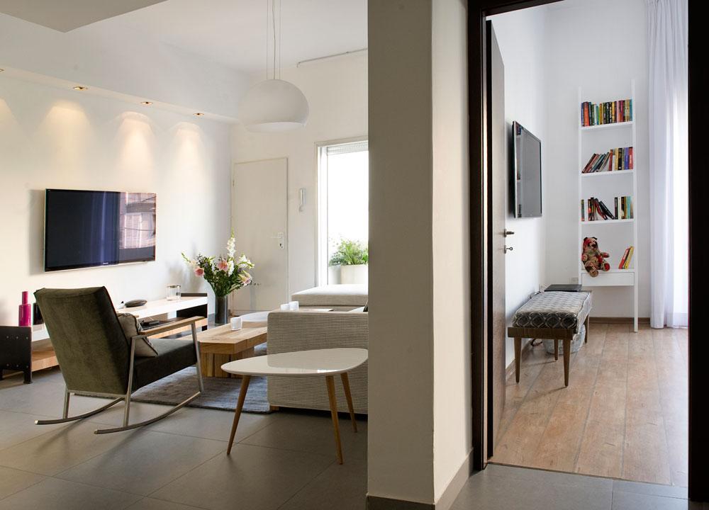 מבט מהמבואה אל הסלון וחדר השינה, שחולקים מרפסת. וילונות לבנים וארוכים מדגישים את גובה התקרה (צילום: גלית דויטש)