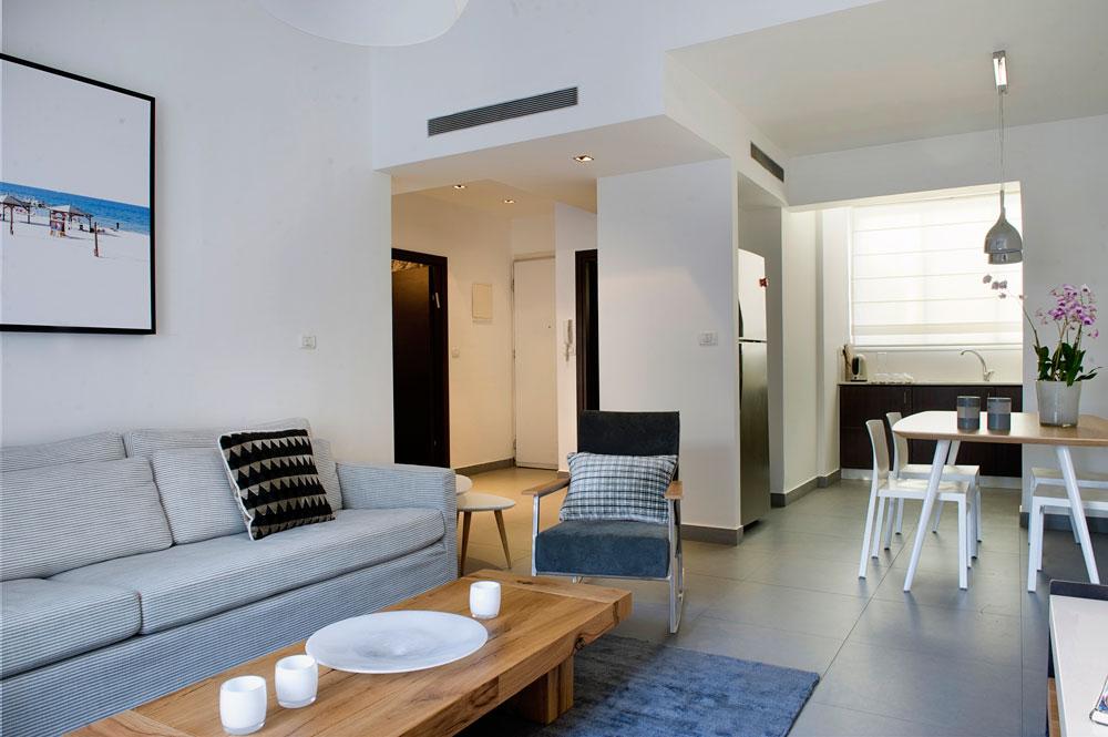 הרצפה אפורה, הקירות הלבנים מדגישים את האור הרב שבדירה, והריהוט נבחר בצבעים בהירים ושקטים (צילום: גלית דויטש)