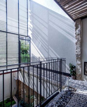 חצר הכניסה המקורה, שמובילה גם לגינה וגם לתוך הבית (צילום: יואב גורין)