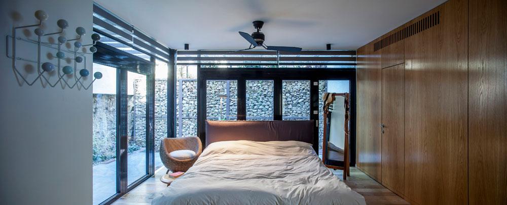 כל חדרי השינה מוארים באמצעות חצרות אנגליות, שמכניסות אור יום מלמעלה. בתמונה חדר ההורים, שלו שני קירות זכוכית. קירות החצרות עשויים מאבנים, פסולת מחצבות מאזור חברון (צילום: יואב גורין)