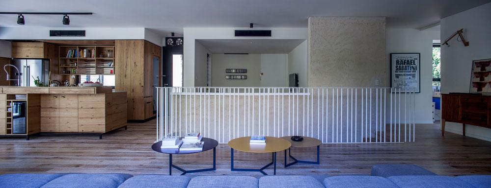 מבט מהספה, לאורך הקומה. משמאל המטבח והיציאה לגינה האחורית, מימין חדר המשחקים של הילדים, שמשקיף אל הגינה הקדמית של הבניין. מאחורי גרם המדרגות חדר משפחה עם טלוויזיה (צילום: יואב גורין)