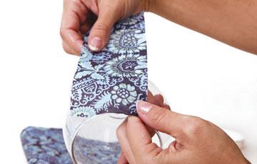 מדביקים את המפיות על כלי הזכוכית (צילום: דנה לנדאו )