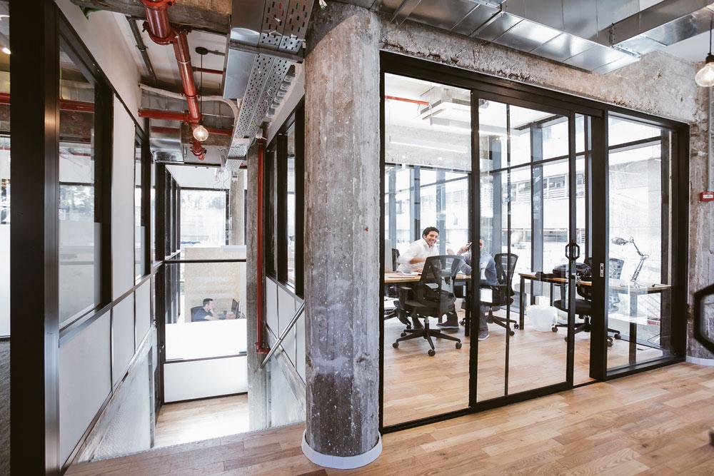 בסך הכל בבניין 420 עמדות עבודה, במשרדים בגדלים שונים. העיצוב דומה בכל סניפי WeWork בעולם: רצפת עץ, תקרה חשופה בסגנון תעשייתי, מסגרות אלומיניום שחורות וקירות זכוכית (צילום: שירן כרמל)