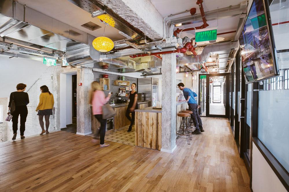פס של זכוכית אטומה מקיף סביב: כשיושבים זוכים העובדים לפרטיות, וכאשר הם עומדים הם ''הופכים לחלק מהקהילה'', כך מסביר בנג'י זינגר, מנכ''ל WeWork בישראל, את התפיסה של החברה. לכן גם מעדיפים כאן לקרוא לשוכרים ''חברים'' (צילום: שירן כרמל)