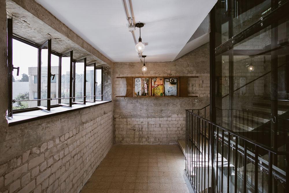 בחדר המדרגות בולט הסגנון התעשייתי. על הקיר אלונקה שעליה צילומי גרפיטי (צילום: שירן כרמל)