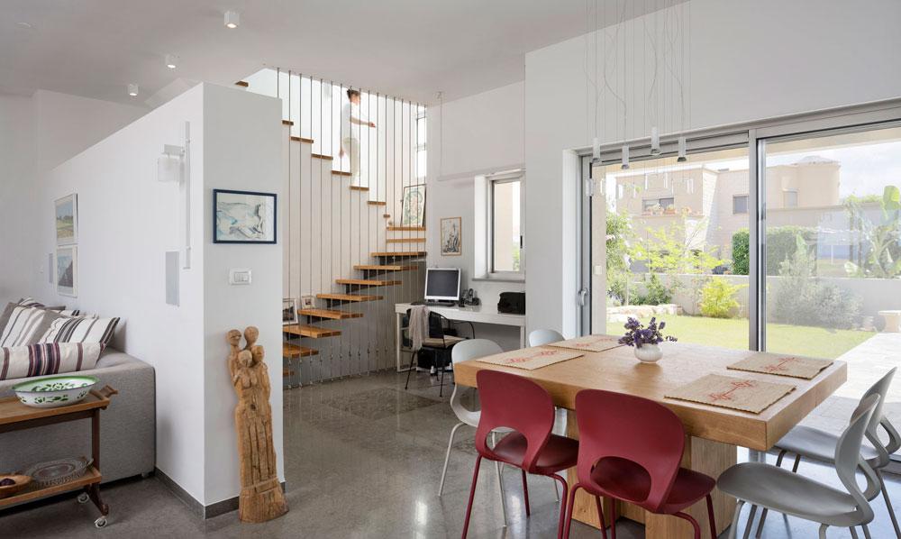 קיר שאינו מגיע לתקרה מפריד בין הסלון לפינת העבודה. גרם המדרגות מוביל לסטודיו עם מרפסת הפונה לים (ראו בתמונה הבאה) ולחדר אירוח המשמש את הילדים והנכדים (צילום: שי אפשטיין )