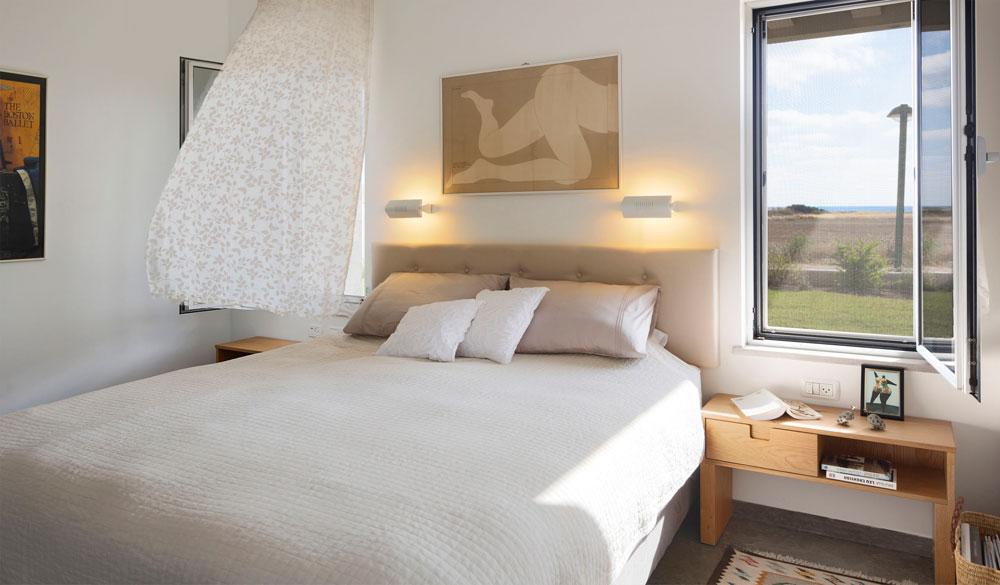חדר השינה של בעלי הבית. מעל המיטה נתלה ציור עירום נשי של האמן האמריקאי מילטון גלייזר. שידות הצד נבנו בהזמנה מעץ אלון (צילום: שי אפשטיין )