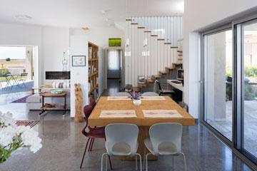 שולחן האוכל מפריד בין המטבח לפינת העבודה. בצד שמאל ניתן לראות את הפסל המשפחתי שגילף בעל הבית (צילום: שי אפשטיין )
