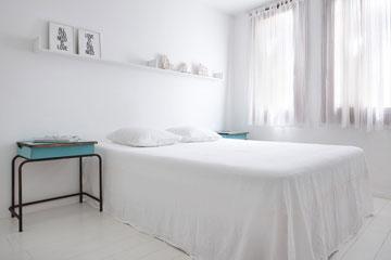 על המדף מעל למיטה ניצבות עבודות של האמן אמנון ליפקין המייצגות מבנים בנווה צדק (צילום: עדי גלעד)