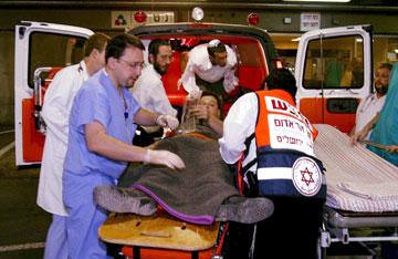 """נובמבר 2002: פינוי פצועים מהפיגוע בציר המתפללים. """"פעם ראשונה שירו עליי"""" (צילום: דן בלילטי)"""