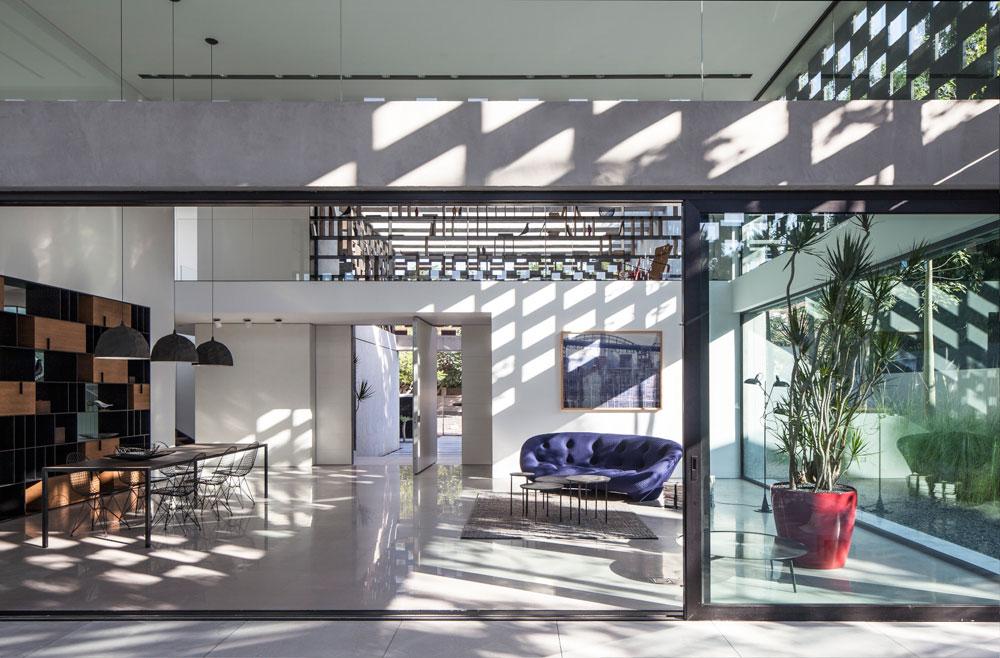 הסלון מתנשא לגובה שתי קומות עם גלריה, וממנו נחשפת החצר עם בריכת השחייה (צילום: עמית גרון)