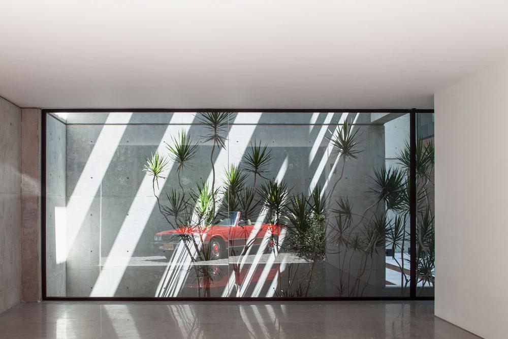 כשנכנסים מהמבואה הביתה, רואים מסך זכוכית רחב המשקיף אל חניון המכוניות (צילום: עמית גרון)