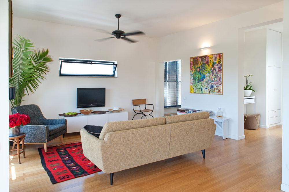 """בסלון רהיטים שונים (משוק הפשפשים, """"פיק אפ"""", """"איקאה""""): ספה, כורסה, שולחן צד, שידת טלוויזיה וכיסא במאים מעור. הפתח שליד הכיסא מוביל לחדר העבודה הנוח שבני הזוג ביקשו (צילום: גלית דוייטש)"""