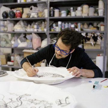 מצייר דוגמאות על עיצוביו (צילום: HAYON Studio)