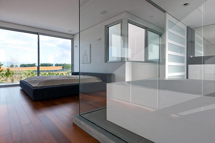 גם ביחידת ההורים השפיע הנוף על ההחלטה לפתוח חלון מהרצפה לתקרה. האמבטיה מוקמה בתוך חדר השינה, וסביבה נבנו קירות זכוכית שקופה. דלת הזזה אטומה מאפשרת להסתיר את האסלה או את האמבטיה, לפי הצורך. מעל כיור מרחף מקיר לקיר, הותקן ארון דלתות הזזה, מחופות זכוכית. למרות המינימליזם שמאפיין את חדר האמבטיה, מתקבל נפח אחסון גדול (צילום: עוזי פורת)