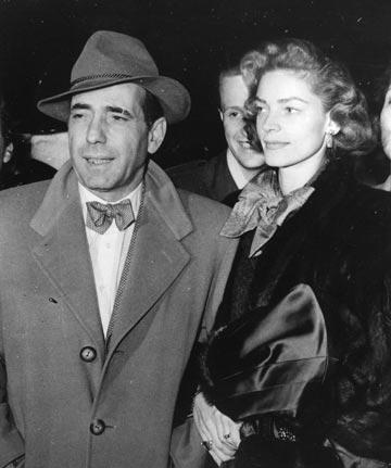 בביקור בלונדון, 1951. מלווה בשלושה אייקונים: רעייתו השחקנית לורן באקול, מגבעת הפדורה ומעיל הטרנץ' (צילום: gettyimages )