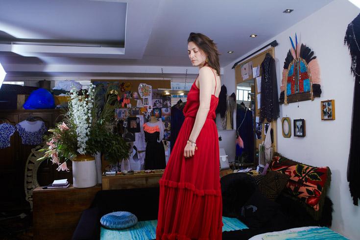 """ליאורה טרגן בביתה, לבושה בשמלה של לילך אלגרבלי. """"אני מאוד מתחברת לדרמה של הבגדים שלילך מעצבת"""" (צילום: ניקיטה פבלוב)"""