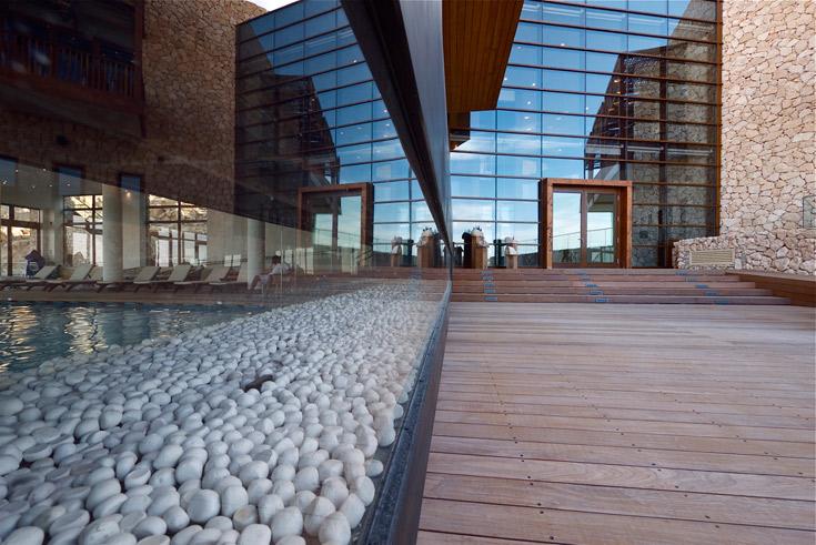 הכניסה למבנה המרכזי של המלון. בריכה משמאל, זכוכית בחזית והרבה עץ. שונה מהעיצוב המקומי של שאר המתחם (צילום: איתי סיקולסקי )