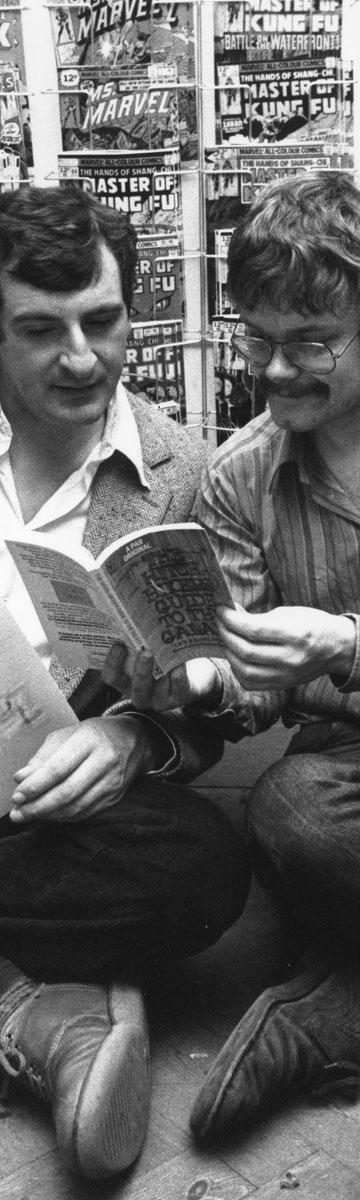 ניק לנדאו (מימין) עם דאגלס אדאמס ב-1979, יושבים מול ערימת קומיקסים, הספר והאלבום של הגלקסיה (צילום: gettyimages)