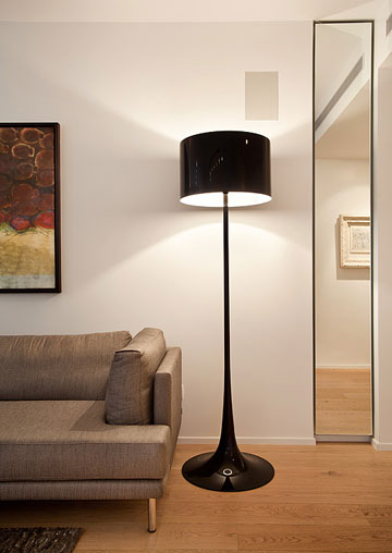 אחת משתי המנורות מתוצרת ''פלוס'', העומדות בסלון לצד ספה אפורה שנרכשה ב''ניס'' בפלורנטין. בכל החללים תאורה שקועה וסמויה, וכבלי החשמל והתקשורת נסתרים מהעין (צילום: סטודיו יונתן בלום)