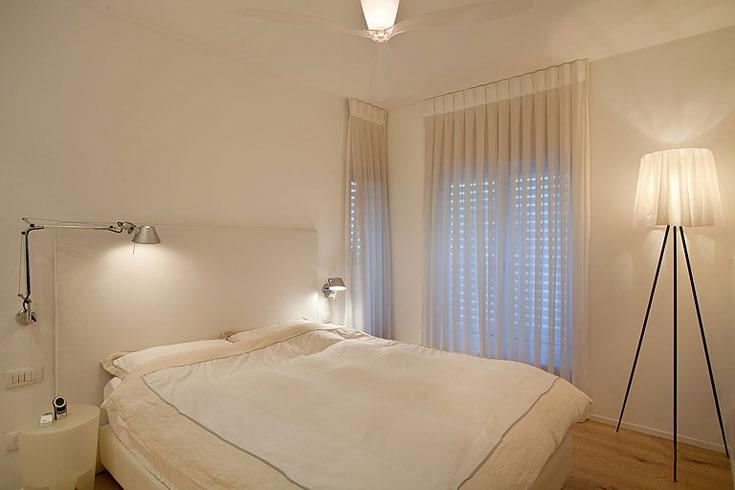 חדר השינה  אף הוא לבן. גב המיטה הגבוה תוכנן אצל רפד, ומשני צידיה מנורות קריאה בשם ''טולומיאו'' מבית ''ארטימידה'' (''קמחי תאורה''). בחדר ניצבת גם מנורה שעיצב פיליפ סטארק (''קרני תכלת''), ומעל מרחף מאוורר תקרה שקוף מתוצרת ''לוצ'ה פלאן'' האטלקית  (צילום: סטודיו יונתן בלום)