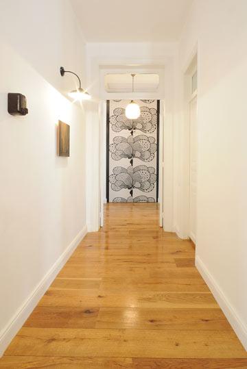גופי התאורה הם פריטי וינטג'. במסדרון תלויות שש מנורות שנראות כמו פנסי רחוב (צילום: נעמה כנפו, סטודיו Architype)