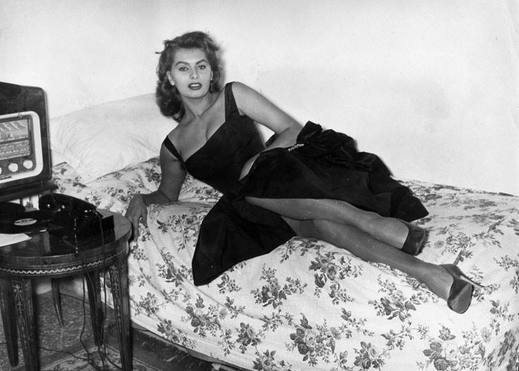 סופיה לורן בשמלה שחורה מתרווחת על מיטה, 1957 (צילום: Gettyimages imagebank)