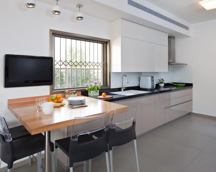 שולחן האוכל במטבח - שממוקם בלב הבית - נבנה מעץ אלון טבעי והוצב מול נוף ירוק (צילום: שי אפשטיין )