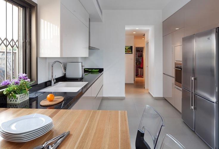 המעבר מהחלל הציבורי לחלל הפרטי בבית נעשה דרך המטבח. כדי ליצור מעבר רחב ומזמין עוצב המטבח כשני קווים מקבילים: דלתות הארונות נצבעו בגוון נס קפה בגימור מבריק, והארונות ממול בלבן מבהיק. הקיר חופה בזכוכית לבנה, כניגוד למשטח העבודה, שעשוי שיש גרניט שחור (צילום: שי אפשטיין )