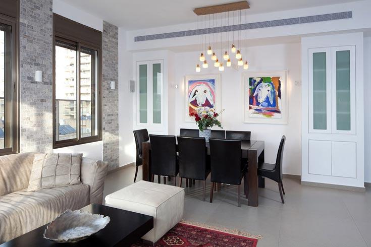 נישות גבס עם דלתות לבנות מבריקות תוחמות שתי תמונות של קדישמן, שיוצרות כתמי צבע על הקיר הלבן. הריהוט מגדיר את אזור פינת האוכל (צילום: שי אפשטיין )
