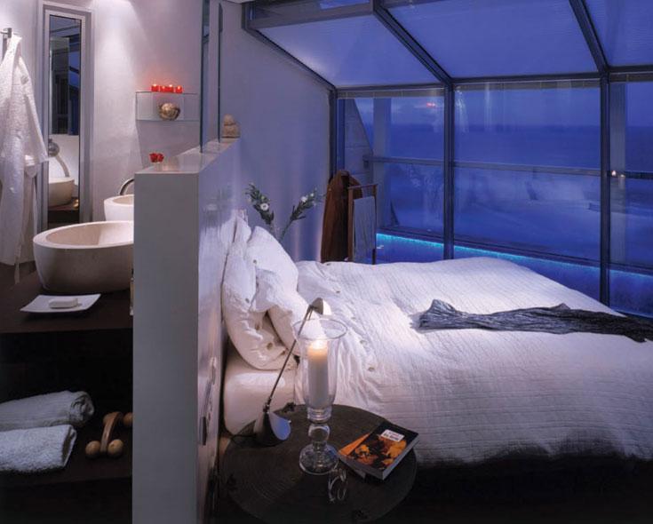 חדר שינה ורחצה בתכנון דור קונפינו. שני החללים הפכו לאחד: גב המיטה הוא קיר נמוך, שמצידו השני תלויים עליו כיורים וארון חדר הרחצה. בתוך הקיר ''שתולות'' שתי מראות. אור היום שנכנס מחלונות חדר השינה מאיר גם את המקלחת והשירותים. בשעות הלילה, בזכות פס התאורה הכחול, החוץ ממשיך את הפנים כך שנוצרת אשליה של חלל גדול יותר (צילום: יונתן רשליין)