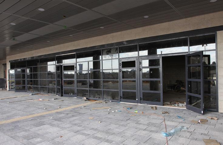 הכניסה. קירות המסך, יחד עם חיפויי לוחות האלומיניום האפורים של הגגות, משווים לאצטדיון מראה של חברת הייטק (צילום: עידו ארז )