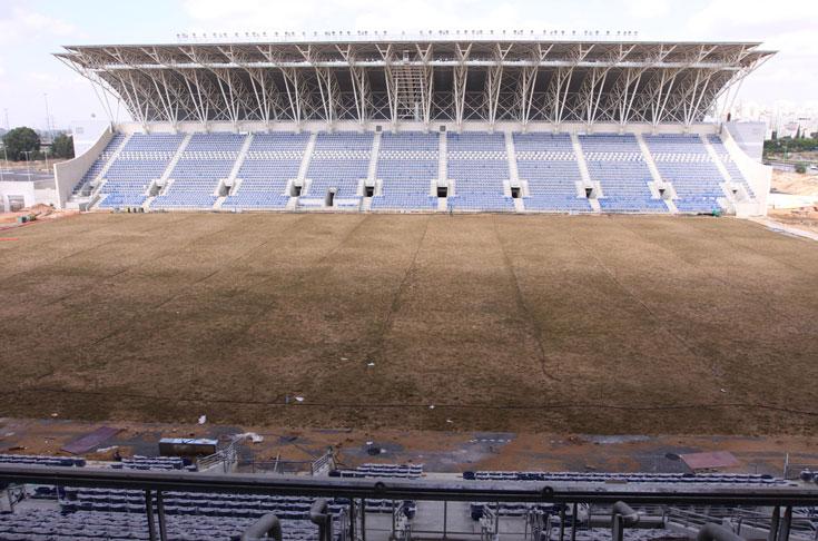 הדשא. רק נשתל ומצוי בשלבי קליטה. מדוע לבזבז במקום דשא סינתטי? האדריכל אומר שהדבר נובע מדרישות פיפ''א ואופ'א (צילום: עידו ארז )