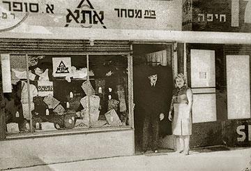 בני הזוג סופר בפתח חנותם ברמתיים הפעילה עד היום (צילום: אוסף יהודית מילוא)