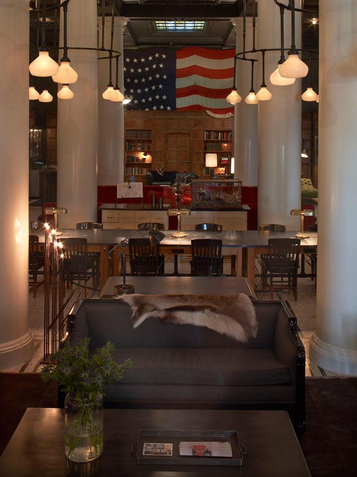 """הבר מוביל לספרייה המעוצבת כמו """"ספריה ביתית מפוארת  בפארק אבניו"""". דגל ארה""""ב משקיף על כל הלובי (צילום: ace hotel)"""