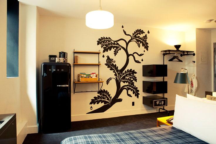מקרר של פעם בצבע שחור, שטיחים מקיר לקיר ומנורות עומדות. חדר זוגי במלון (צילום: Douglas Lyle Thompson)