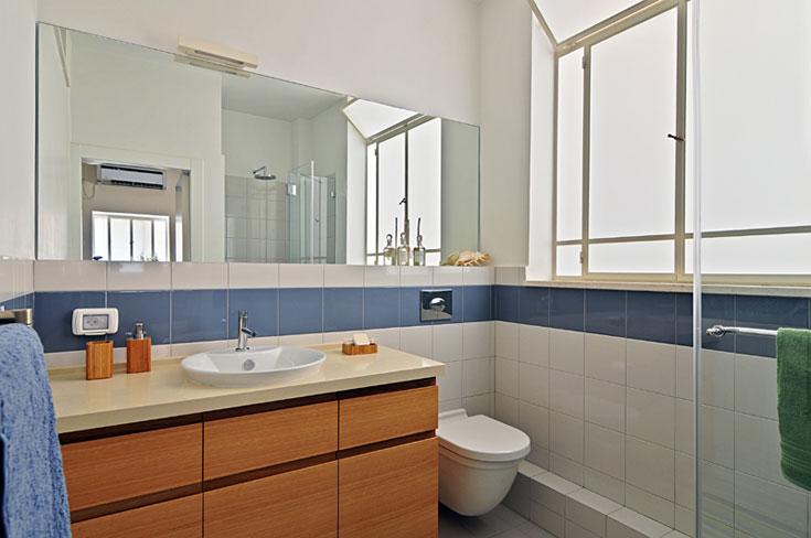 בחדרי הרחצה אריחים לבנים עם פס דקורטיבי בצבע כחול, צבעים שנבחרו כי הם ''לא נמאסים''. את הארונות עשה נגר מאלון טבעי, כמו הפרקט והשידה הסלון (צילום: שי אדם)