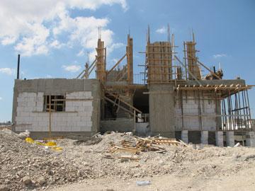 בית בבנייה בשכונת ההרחבה. את אווירת השקט העצובה של הקיבוץ מחליפים הלמות הפטישים  (צילום: מיכאל יעקובסון)