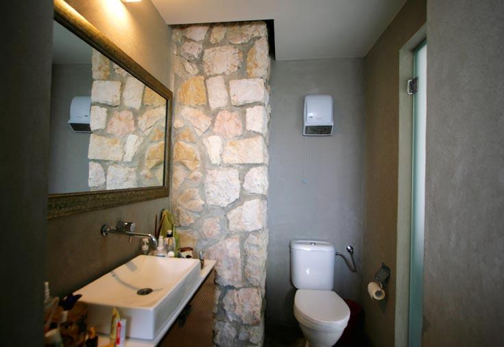 קירות אבן שהיו חיצוניים והפכו לפנימיים בתהליך ההרחבה, נשמרו כמות שהם והפכו לאלמנט דקורטיבי בשני חדרי האמבטיה (צילום: גיא יצחקי)
