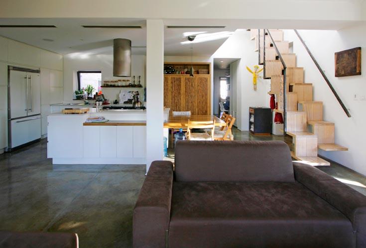 המטבח נצבע לבן והאי בנוי משני דלפקים בצורת ריש (נגרות: אורי לאופר). מימין המדרגות העולות לגג, והן צרות במיוחד: בכל מדרגה יש מקום לרגל אחת (צילום: גיא יצחקי)