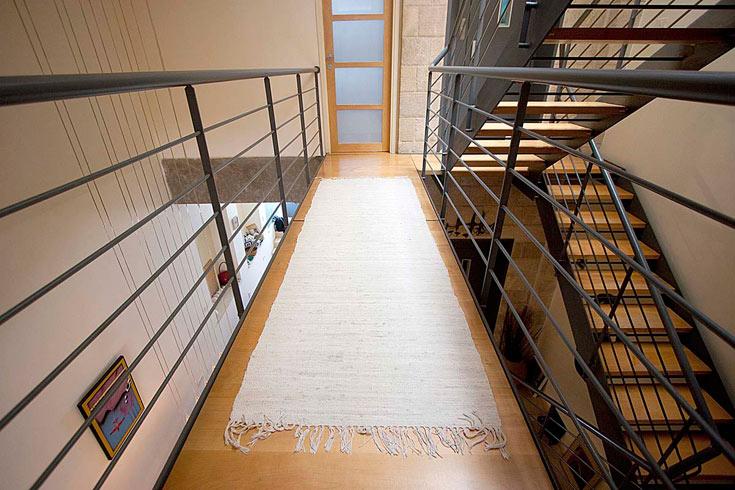 גשר עשוי פלדה ועץ מחבר בין חדר ההורים וחדר העבודה, הממוקמים משני צדי הבית (צילום: גיא יצחקי)